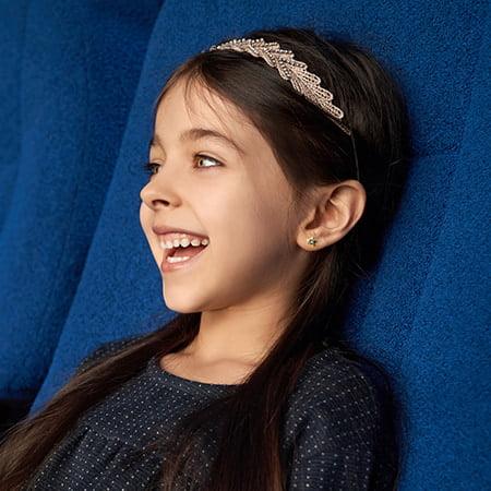 przekłuwanie-Uśmiechnięta dziewczynka z kolczykiem w uchu